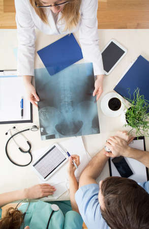 physician: Three physicians holding xray photo of spine
