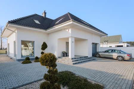exteriores: Residencia blanca grande con garaje para coche nuevo plata