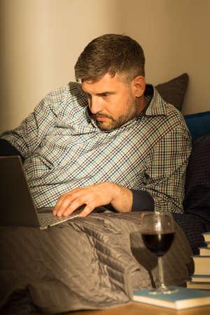 tomando vino: Hombre que practica surf en el Internet en la tarde Foto de archivo