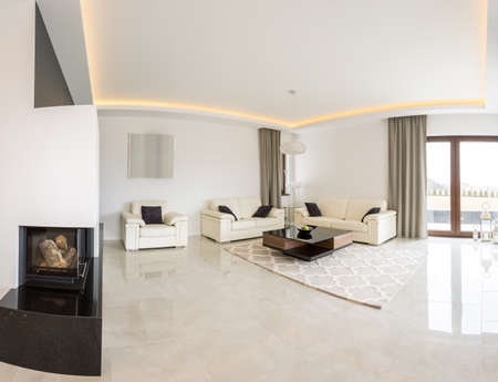 Spacious bright living room with fireplace and marble floor Archivio Fotografico