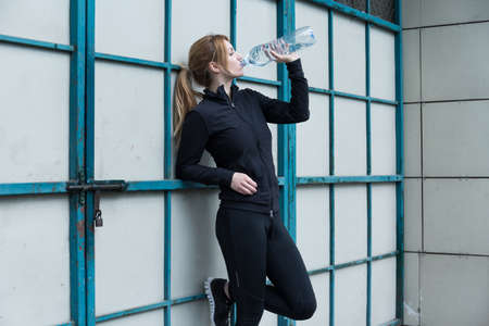 electrolytes: Female runner holding a bottle of water