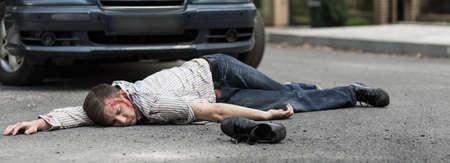 Dead young man is lying on street Standard-Bild