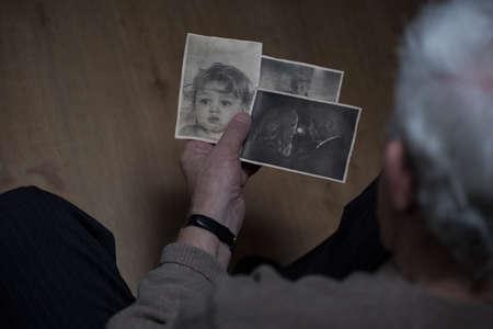 hombre solo: Hombre mayor mirando fotograf�as en blanco y negro