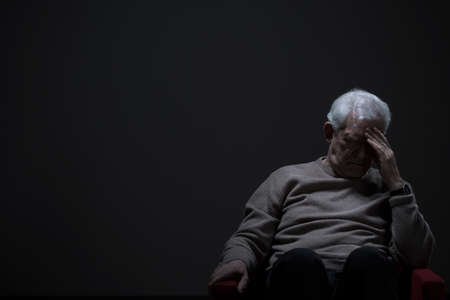 Despairing senior man on a dark background Фото со стока