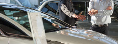 car salesperson: Panorama of car dealer presenting new elegant modern car