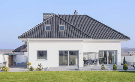 大きな窓と緑豊かな庭園を持つ巨大な白い家
