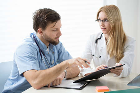 diagnosing: Two young experienced doctors diagnosing the patient