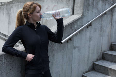 electrolytes: Female jogger standing by the stairs drinking water