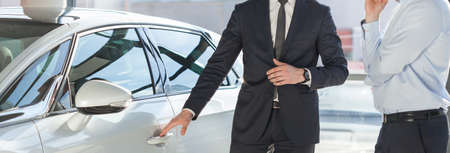 car salesperson: Young man in suit standing by his modern luxurious car