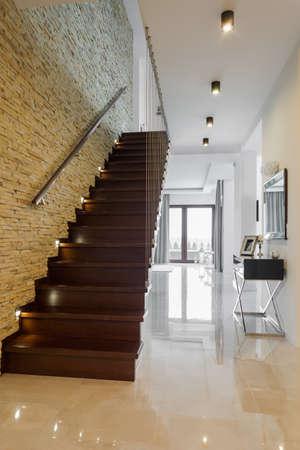 Pasillo de estilo clásico con suelo de mármol y escaleras de madera