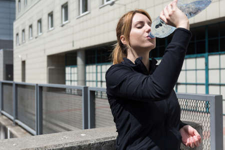 electrolytes: Attractive fitness woman drinking water after running
