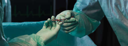 blade cut: Closeup of surgeons hands holding pliers during operation