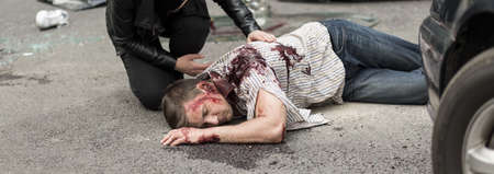 the unconscious: Unconscious young man is lying on street