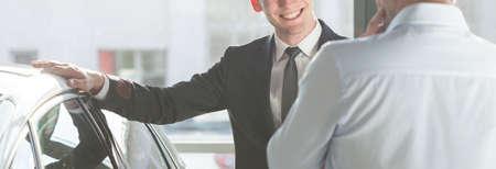 Uomo sorridente in tuta azienda mano sulla sua nuova macchina moderna Archivio Fotografico - 43692474