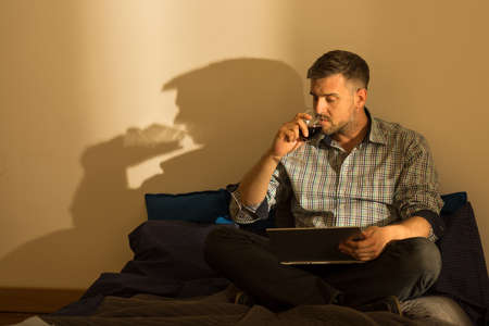 work addicted: Man using laptop and drinking wine at evening Stock Photo