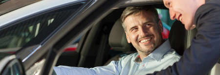 Happy man sitting in the car and smiling to his friend