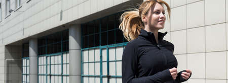 blonde woman: Panorama of a beautiful woman exercising outdoors Stock Photo