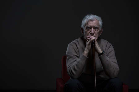 soledad: Anciano pensativo sentado en una habitación oscura Foto de archivo