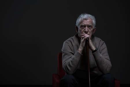 Doordachte oudere man zit in een donkere kamer