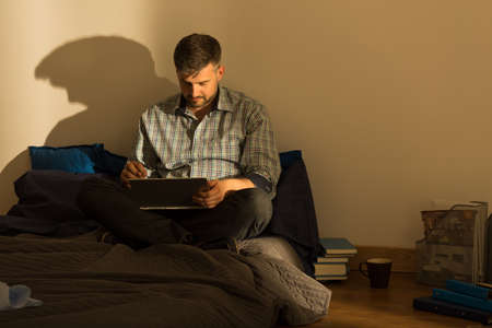 work addicted: Image of man using laptop in bed
