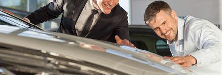 hombres guapos: Dos hombres guapos elegantes admirando nuevo coche brillante de lujo Foto de archivo
