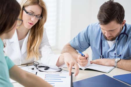 Ba bác sĩ trẻ có kinh nghiệm kiểm tra kết quả xét nghiệm của bệnh nhân