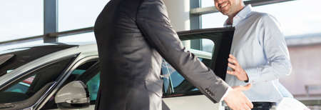 Panoramic view of young elegant man getting into the car