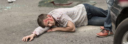 recovery position: Seriously injured man is lying on street
