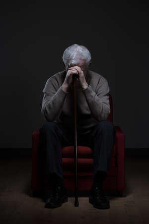 Hopeloze gehandicapte gepensioneerde in een leunstoel Stockfoto