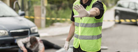 ban aid: Policeman is banning entrance on car accident area Stock Photo