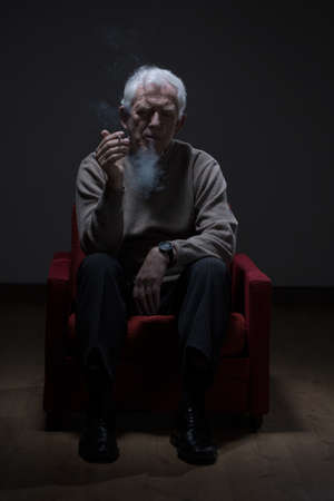 senior smoking: Senior man sitting in an armchair and smoking cigarette Stock Photo