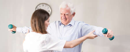 men exercising: Hombre mayor ejercicio con pesas durante la rehabilitación en casa Foto de archivo