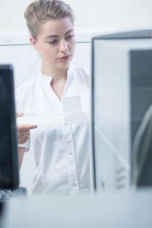 bata blanca: Mujer en la capa blanca que trabaja en laboratorio