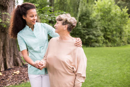 care at home: Elder woman and caregiver walking in the park Stock Photo