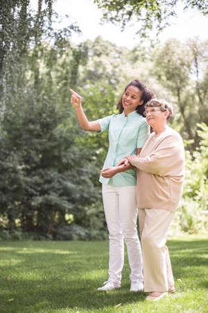 persona de la tercera edad: Una más vieja mujer y la enfermera que da un paseo en el parque