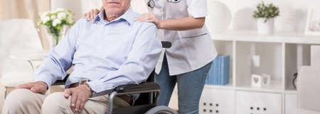 Gepensioneerde zit in een rolstoel en hulp verpleegkundige Stockfoto