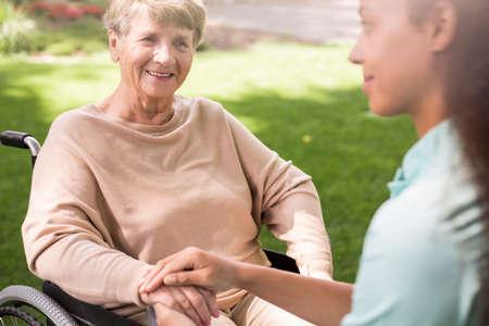 caring nurse: Senior woman and caring nurse in the garden