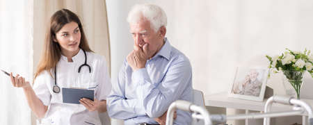 geriatric care: Patient talking with young doctor at home Stock Photo