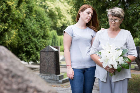 graves: Picture of elderly woman visiting grave of her husband Stock Photo