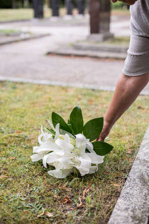 graves: Close up of woman leaving white lilies on grave Stock Photo