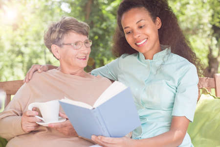 retirement homes: Senior woman and caregiver reading book in the garden