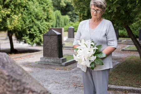 묘지 들고 흰 백합에 성숙한 여자의 사진 스톡 콘텐츠