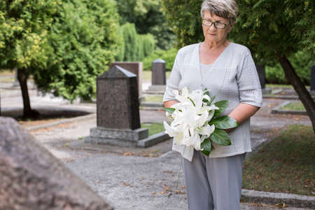 Photo of mature woman on cemetery holding white lilies