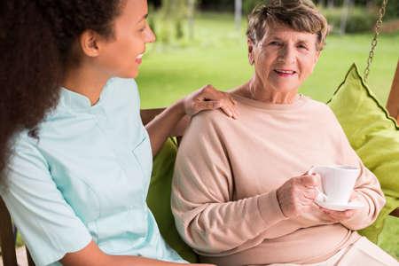 caring nurse: Caring nurse and elder woman in the garden