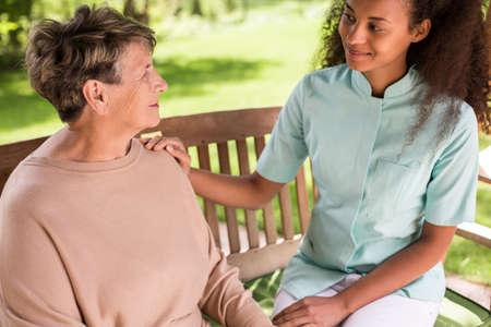 Senior woman and carer spending time outside