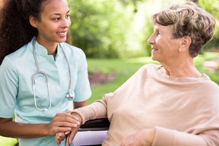 doctor care: Senior woman and doctor spending time in the garden Stock Photo