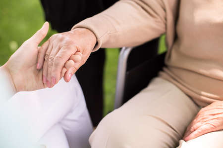eldercare: Close-up of nurse supporting disabled senior woman Stock Photo