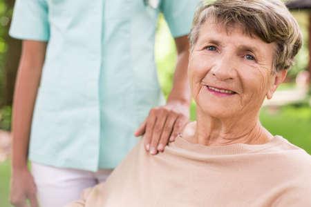 persona de la tercera edad: Mujer mayor y enfermera de cuidado en el jardín