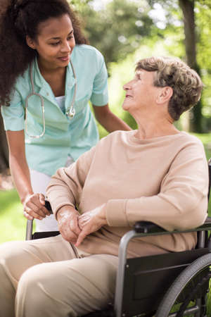 Doctor and disabled woman spending time outdoors