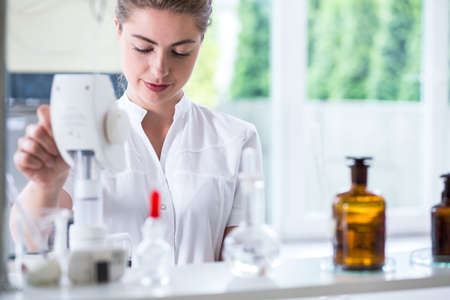 research science: Young female lab technician doing chemistry experiment